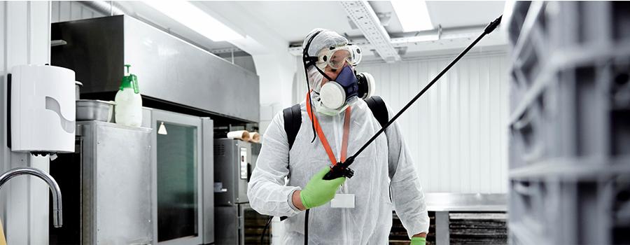 Technician applying electrostatic disinfectant